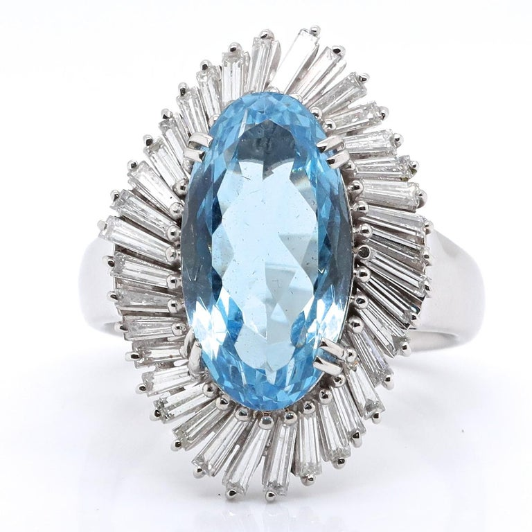 This ring is glamorous enough to be worn by a Hollywood star or a trendy newscaster. This is a desirable Vintage Aquamarine Diamond Platinum Ballerina Cluster Ring. The center stone is an Oval cut aquamarine, 6.48 carats. Accompanied by 36 tapered
