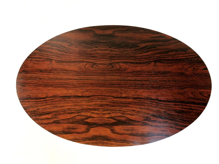 Arkana rosewood occasional table  Occasional table by Maurice Burke for Arkana.  Oval shaped rosewood top with a rich grain which sits on a heavy steel tulip base.  Made in the UK. Stamped by the maker, circa 1960s.  Dimensions: 57 W x 37 D