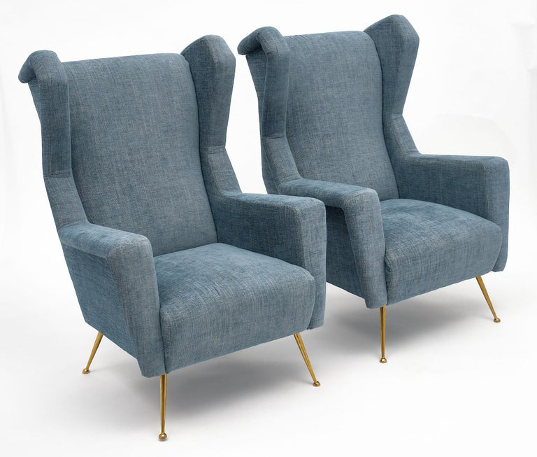 """Pair of vintage armchairs or """"bergeres"""" in the style of Carlo di Carli. They have been newly upholstered in a blue wool blend mix. We are drawn to the solid gilt brass legs and strong proportions of this pair."""