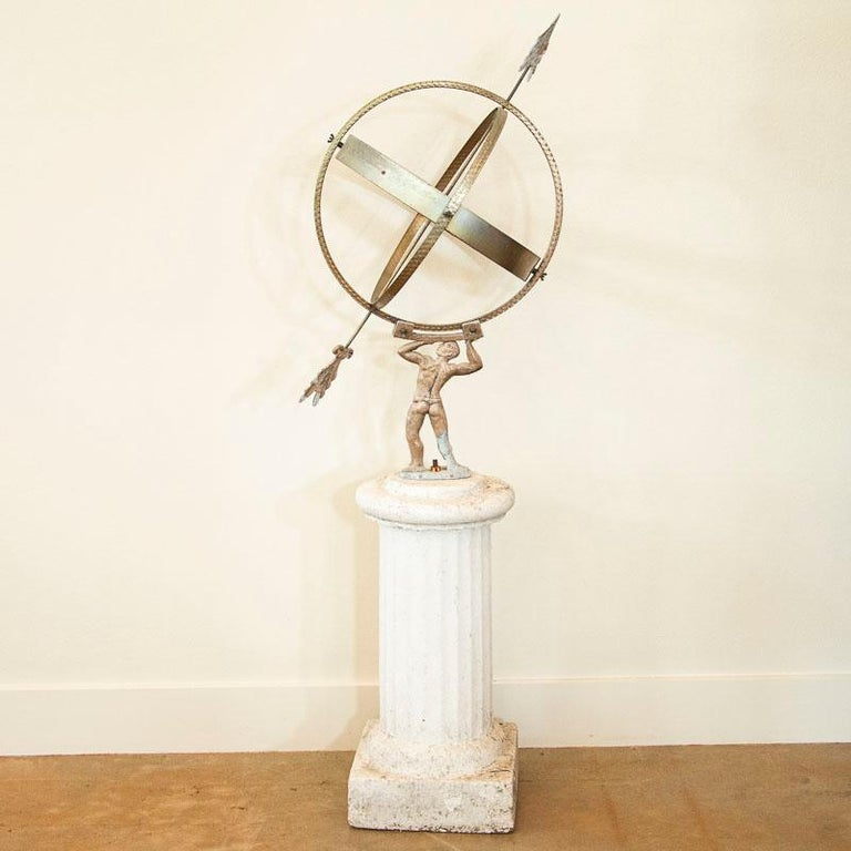 This vintage painted globe shaped garden ornament, called an armillary, is made up of metal bands, pierced by an arrow and supported by a mounting bracket. The base is an image of Atlas holding up the world. These