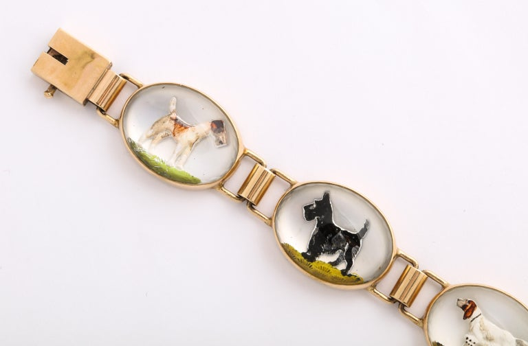 Oval links of 14 Kt gold and rock crystal hold cuddly Scottie Dogs, Terriers and Hounds their images carved and transfixed on a mother of pearl background, The bracelet is a whimsical conversation piece made c. 1930 in the United States. I have not