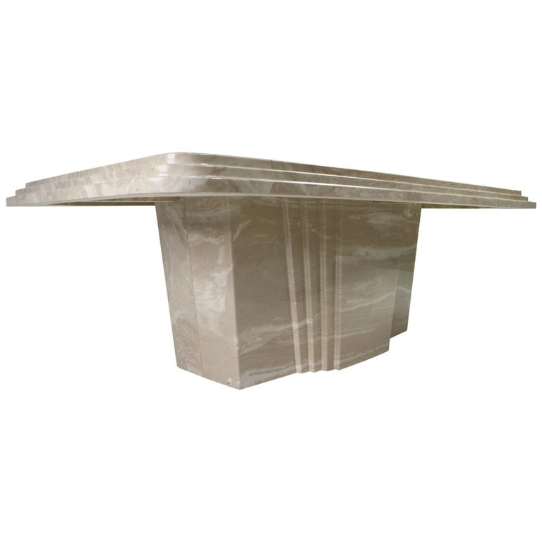Outstanding vintage 1970s Art Deco coffee table. The monumental coffee table is made of Italian travertine. The stone closely resembles marble but has an earthy gray/beige tone. The tabletop features a triple beveled edge and rounded corners. The