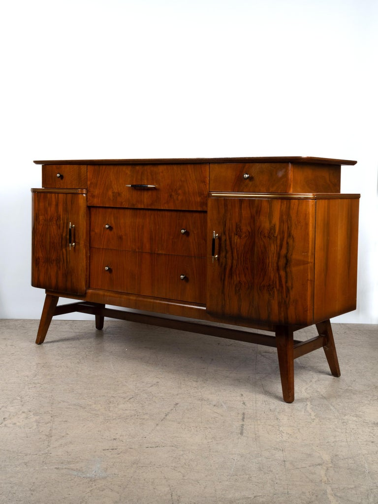 Figured walnut midcentury credenza sideboard by British manufacturer Beautility England, circa 1960. An elegant sculptural piece in the Art Deco manner. The sideboard is constructed in mahogany and finished in beautiful book matched burr (burl)
