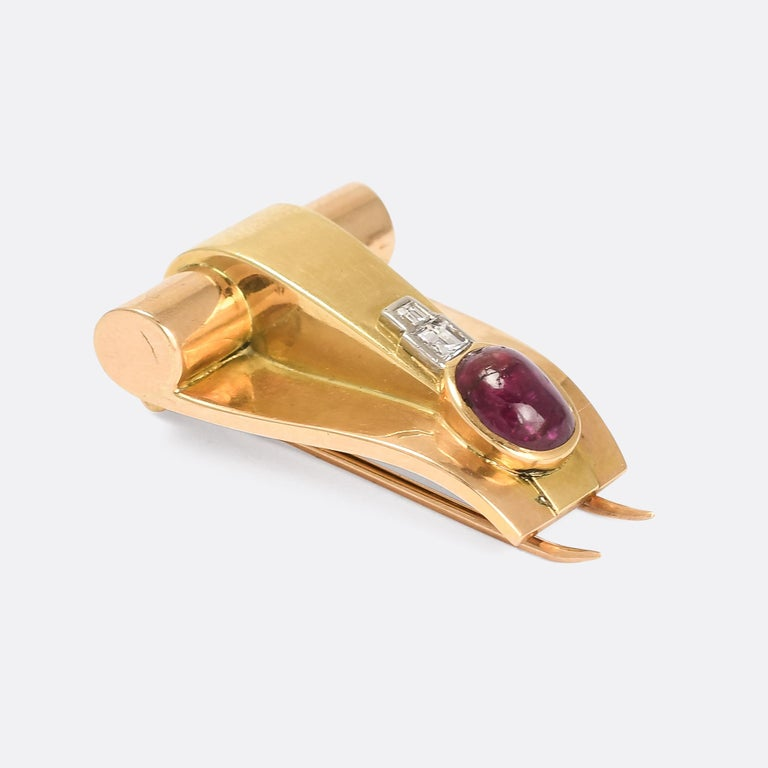 A striking Art Deco brooch set with a natural cabochon ruby and diamond centrepiece. The design is reminscent of a scroll or buckle (I can't quite make up my mind which..) and is very typically Deco in style. It's crafted in 18 karat gold, with