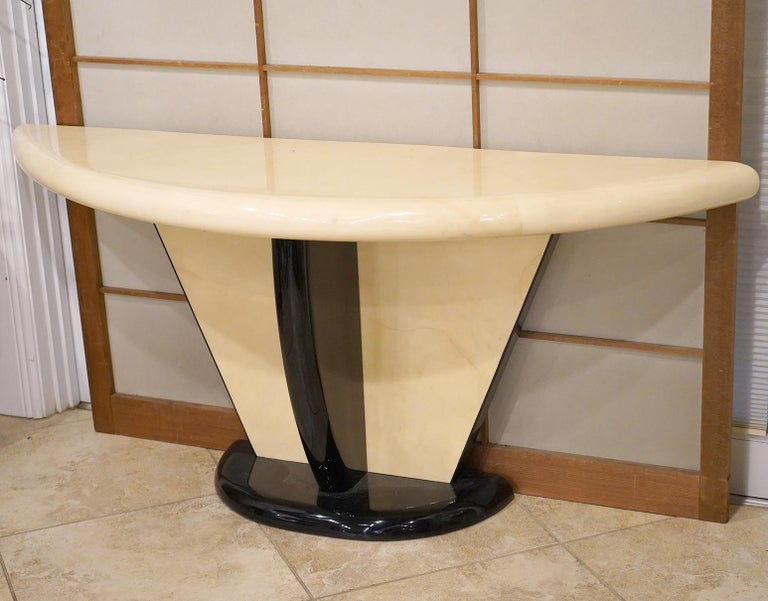 The striking design of this Art Deco inspired Karl Springer style demilune console table combines the warm and nuanced surfaces of lacquered goatskin parchment with high gloss ebonized structural elements. Perfect craftsmanship adds to the