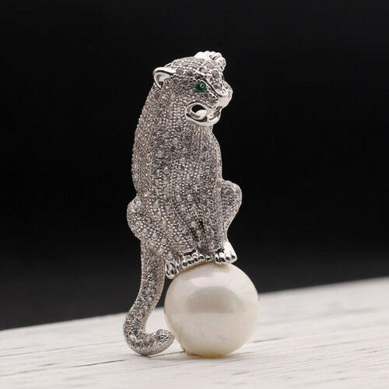 Beautiful, Stylish and finely detailed Jaguar Panther Brooch encrusted with sparkling Faux Diamond Ice Crystal Rhinestones, sitting on a 15mm faux white Pearl. White Gold plated mounting; pin measures  approx. 2'' Inches Tall x 1'' Inch Wide.