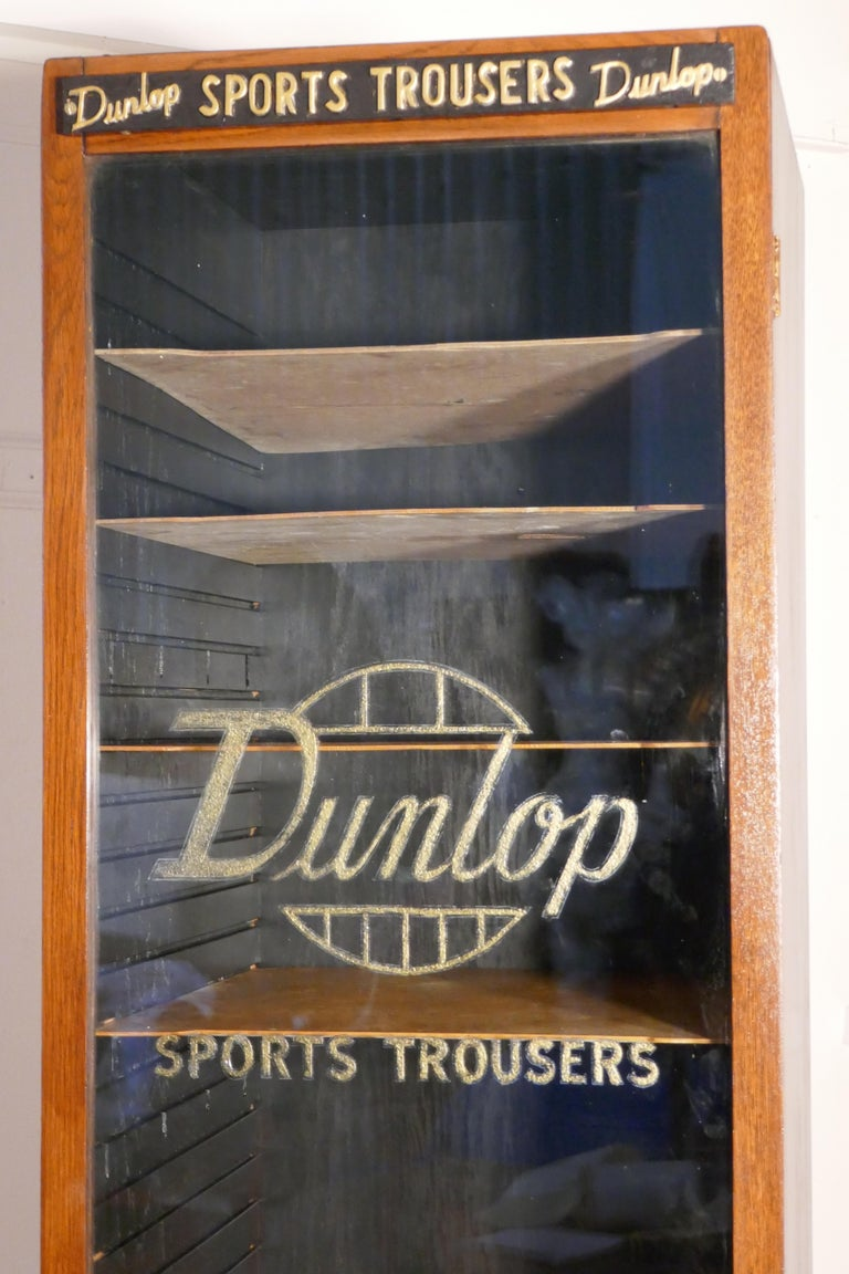Vintage Art Deco tall Haberdashery Dunlop sports cabinet,   This tall and multi shelf cabinet it has a glass fronted door, the cabinet was made to store Dunlop sports trousers, the 9 shelves can be rearranged according to requirements, the