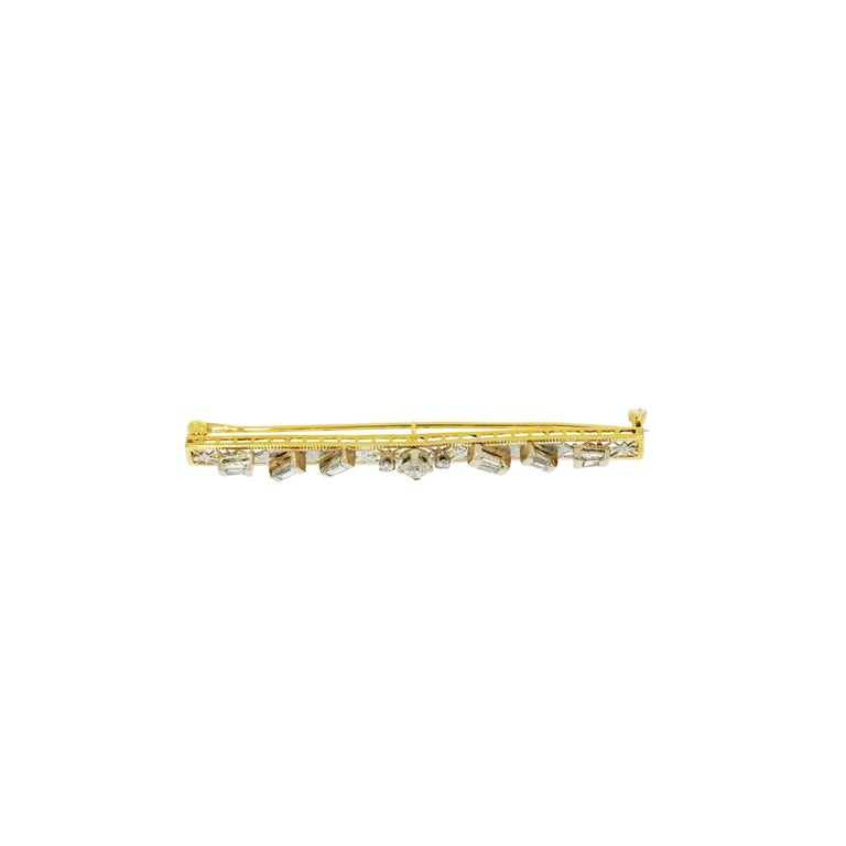 This straight bar brooch has a filigree-work crafted in 14k Yellow Gold, a round Diamond centering and baguette Diamond accents spread along the bar. The center Diamond is an Old mine cut, weighing approximately 0.20 carat and is accompanied by a