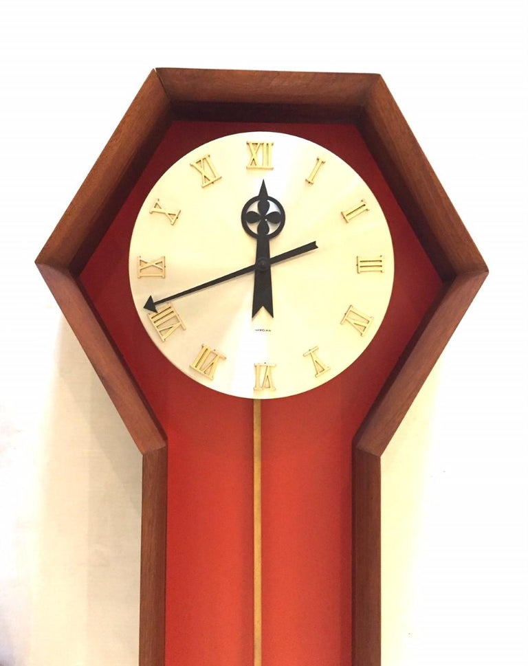 """Vintage pendulum wall clock designed by Arthur Umanoff for Howard Miller. The """"Meridian"""" clock features aspects of Danish Modern design with a walnut wood case with a rare orange backing, brushed silver tone face, and brass pendulum. Raised roman"""