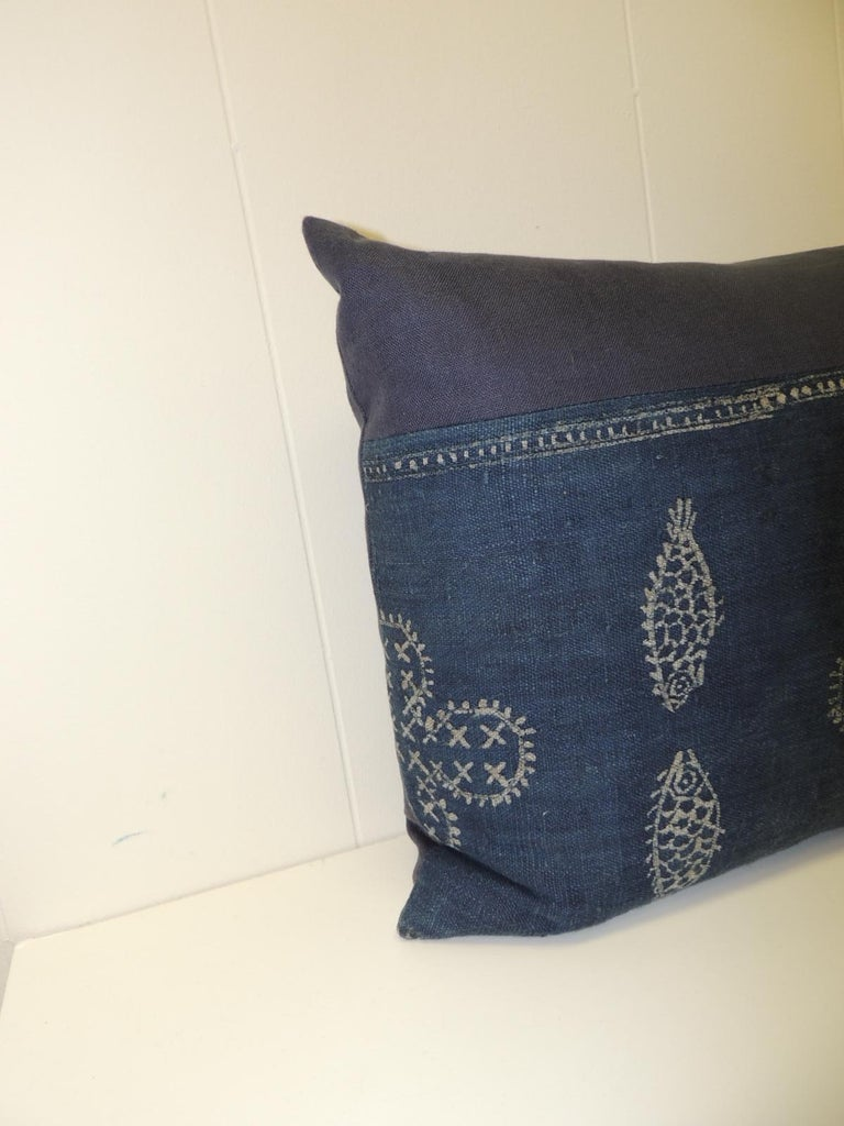 Artisanal indigo textile hand-blocked with white on blue creating a motif of fishes (different kind of) and flowers. Asian hand-blocked textile throw pillows embellished with a blue linen frame with the same textile as backings. Vintage decorative