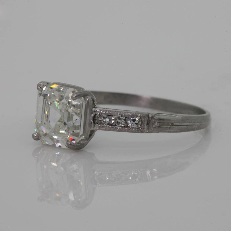 A beautiful 1.80 carats old cut corner Emerald Cut Diamond a.k.a. Asscher cut, G.I.A. I color - VS2  clarity;  in a platinum setting accented with six old Single Cut Diamonds.  The ring is adorned with milgrain and the band is enhanced with a ridge