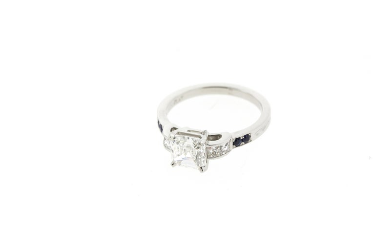This asscher diamond engagement ring is made in platinum and features four additional channel-set side diamonds as well as four deep blue sapphires. A raised gallery and milgraine accents make this beautiful ring a must-have.   Please note that each