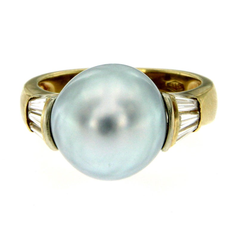 Stunning cocktail ring set in 18k yellow gold. It features a center 12 mm Great Quality South Sea Pearl framed by six tapered baguette cut diamonds for a total weight of 0,60 carat graded F color Vs clarity. Origin Italy, circa 1980  CONDITION: