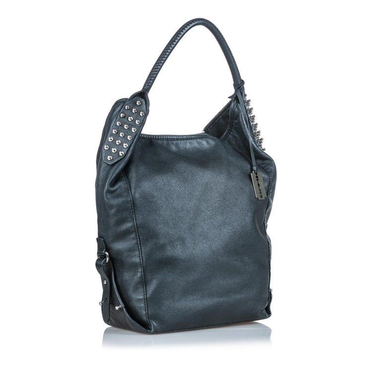 This hobo bag features a leather body with side stud details, a rolled leather strap, an open top with a magnetic closure, and an interior zip pocket. It carries as AB condition rating.  Inclusions:  This item does not come with