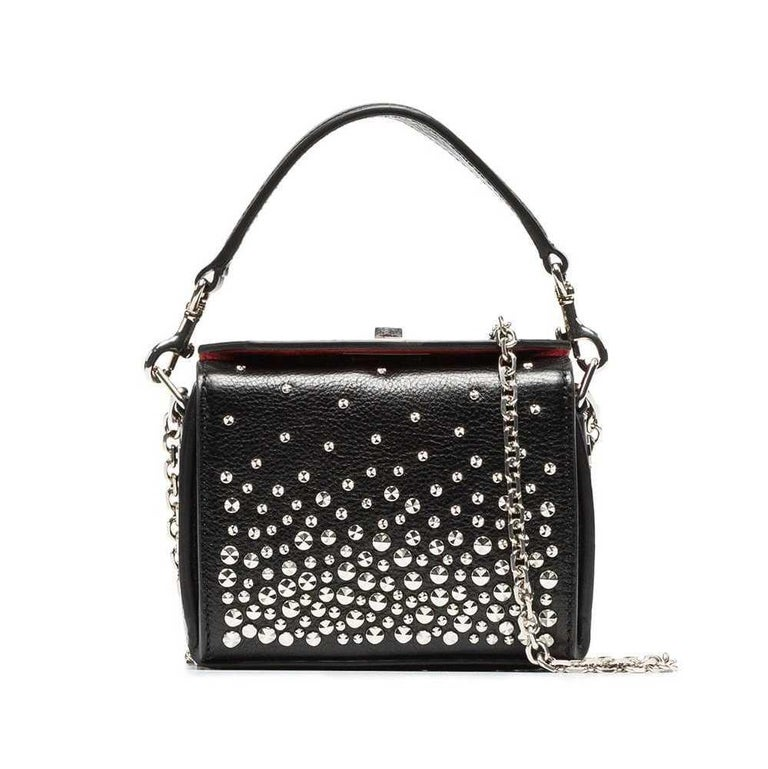 This crossbody bag features a studded leather body, a flat leather top handle, a silver-tone chain strap, and a fold-over top with a metal twist lock closure. It carries as AB condition rating.  Inclusions:  This item does not come with