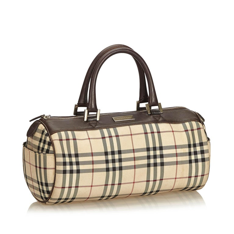 This boston bag features a coated canvas body with leather trim, rolled leather handles, top zip closure, exterior slip pockets and interior slip pocket. It carries as B condition rating.  Inclusions:  This item does not come with