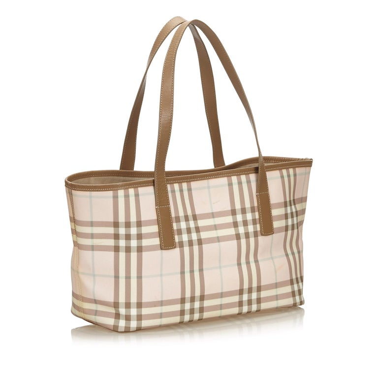 This tote bag features a plaid jacquard body with leather trim, flat leather straps, open top with magnetic snap button closure, and interior zip and slip pockets. It carries as B+ condition rating.  Inclusions:  This item does not come with