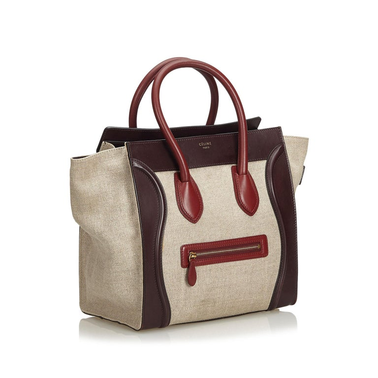 The Phantom tote bag features a canvas body with leather trim, a front exterior zip pocket, rolled leather handles, an open top, and interior zip pocket. It carries as B+ condition rating.  Inclusions:  Dust Bag Dimensions: Length: 31.00 cm Width: