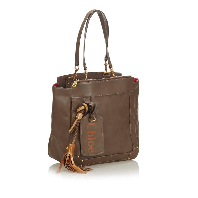 The Eden tote bag features a leather body with a tassel detail, flat leather straps with gold-tone hardware, an open top, a top zip compartment, and interior slip pockets. It carries as B+ condition rating.  Inclusions:  This item does not come with