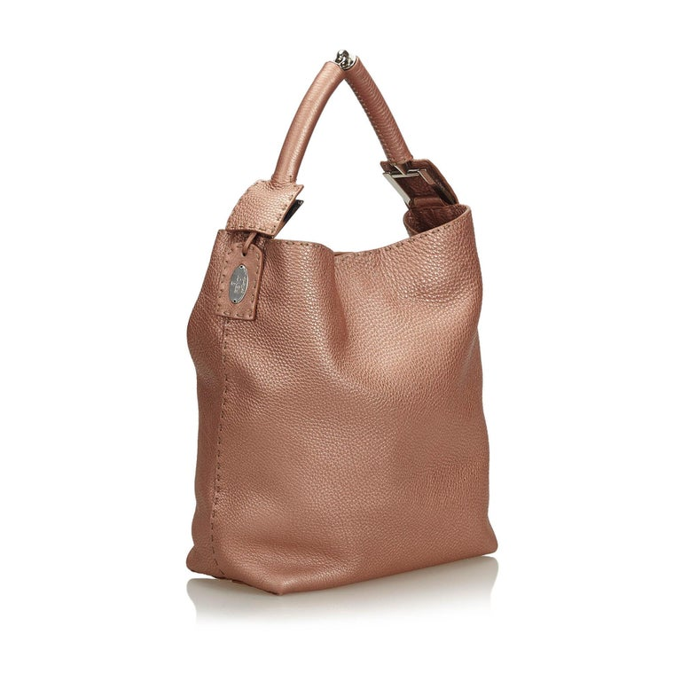 This tote bag features a leather body, a rolled leather handle, an open top with a magnetic closure, and an interior zip pocket. It carries as AB condition rating.  Inclusions:  Dust Bag  Dimensions: Length: 31.00 cm Width: 37.00 cm Depth: 12.00