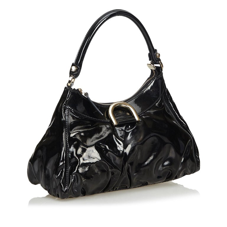 The Abbey D-Ring handbag features a patent leather body with metal hardware, a rolled handle, top zip closure and interior zip pocket. It carries as B+ condition rating.  Inclusions:  This item does not come with inclusions.  Dimensions: Length: