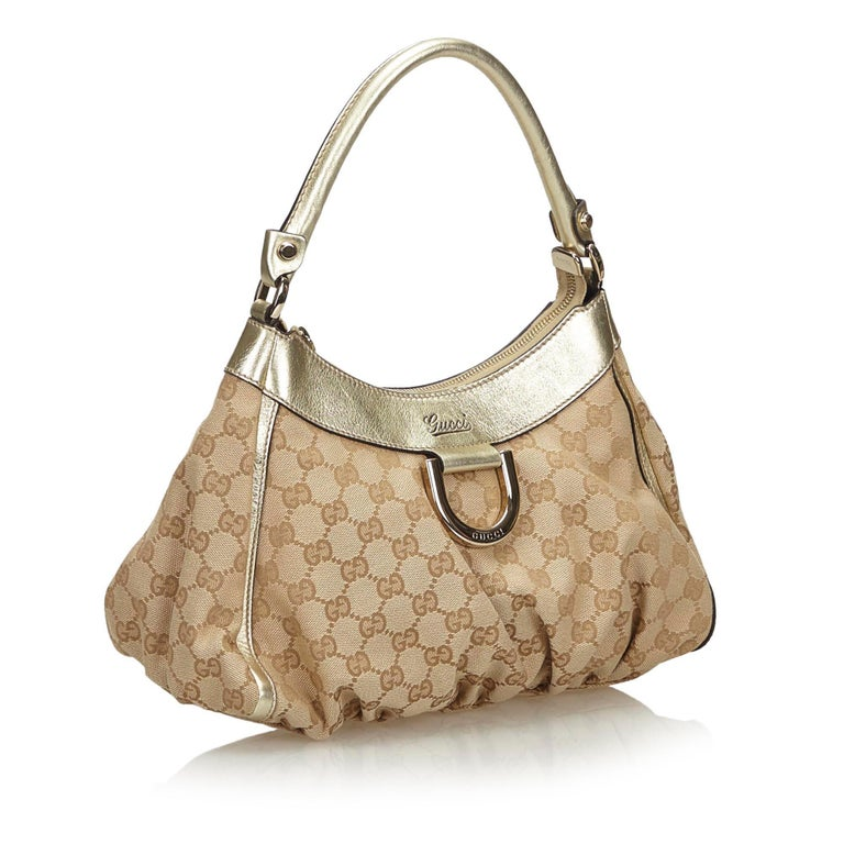 The Abbey D-Ring handbag features a canvas body with leather trim, a rolled leather handle, a top zip closure, fabric lining, and an interior zip and slip pockets. It carries as B+ condition rating.  Inclusions:  Dust Bag  Dimensions: Length: 22.00