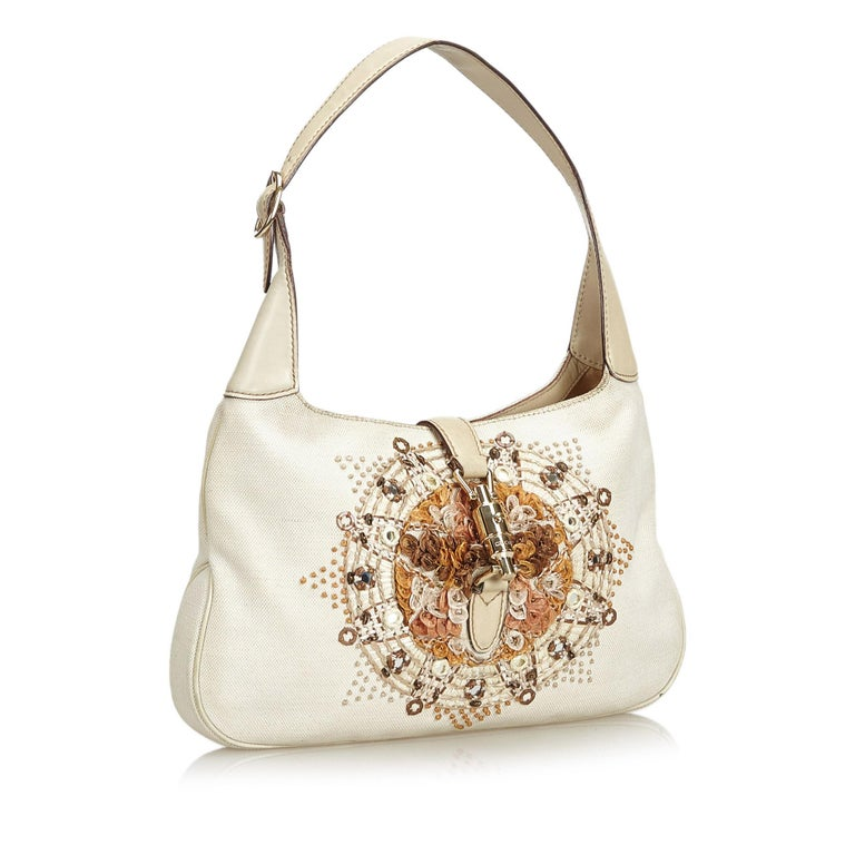 The New Jackie shoulder bag features a embroidered canvas body, flat leather strap, a front strap with piston lock closure, and an interior zip pocket. It carries as B+ condition rating.  Inclusions:  This item does not come with