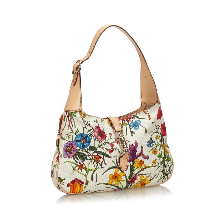 The Jackie shoulder bag features a floral canvas body, a flat shoulder strap, a front strap with a push lock closure, and an interior zip pocket. It carries as B+ condition rating.  Inclusions:  This item does not come with