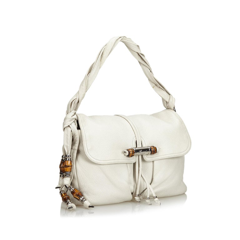 The Jungle shoulder bag features a leather body with bamboo detail, twisted leather handles, a detachable chain strap, a top flap with a magnetic closure, and interior zip and slip pockets. It carries as B condition rating.  Inclusions:  This item