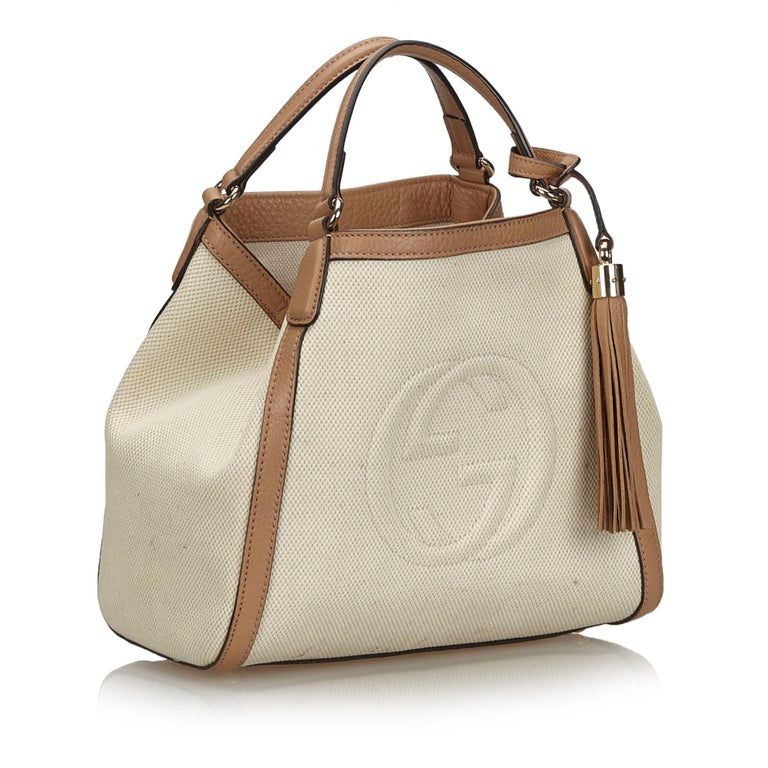 This shoulder bag features a canvas body with leather trim, flat leather handles with a tassel detail, an open top with a lobster claw closure, and interior zip and slip pockets. It carries as B+ condition rating.  Inclusions:  This item does not