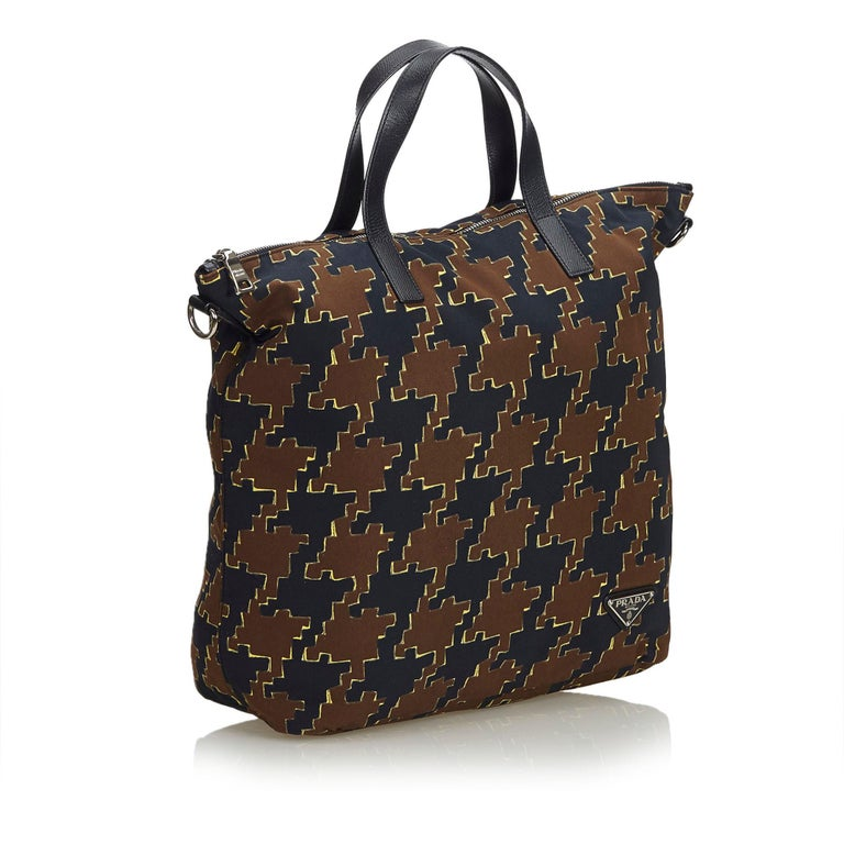 This tote bag features a nylon body, flat leather straps, a detachable flat strap, a top zip closure, and an interior zip pocket. It carries as B+ condition rating.  Inclusions:  Dust Bag Authenticity Card  Dimensions: Length: 32.00 cm Width: 31.00