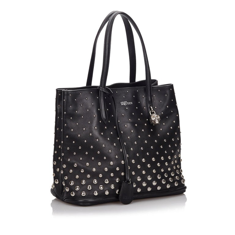 This tote bag features a studded leather body, flat leather straps, a silver-tone skull padlock, a clochette, an open top, and interior zip and slip pockets. It carries as B+ condition rating.  Inclusions:  Padlock Key Dimensions: Length: 28.00
