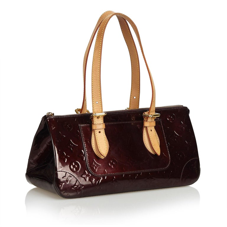 The Rosewood features Vernis leather, adjustable flat vachetta straps, an exterior pocket, a top zip closure, and interior flat pockets. It carries as B+ condition rating.  Inclusions:  This item does not come with inclusions.   Louis Vuitton pieces