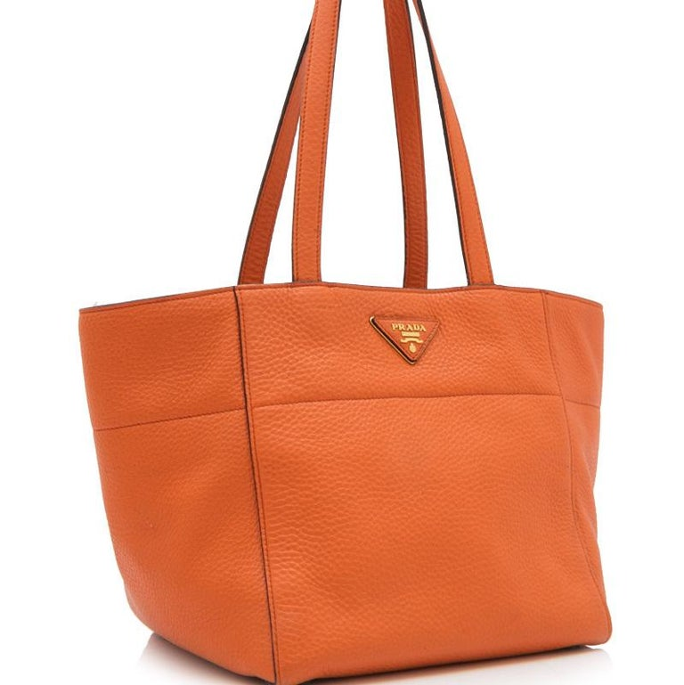 This tote bag features a vitello daino leather body, flat leather straps, and an open top with a concealed magnetic snap tab closure, protective leather feet, fabric lining, and interior zip and slip pockets. It carries as AB condition