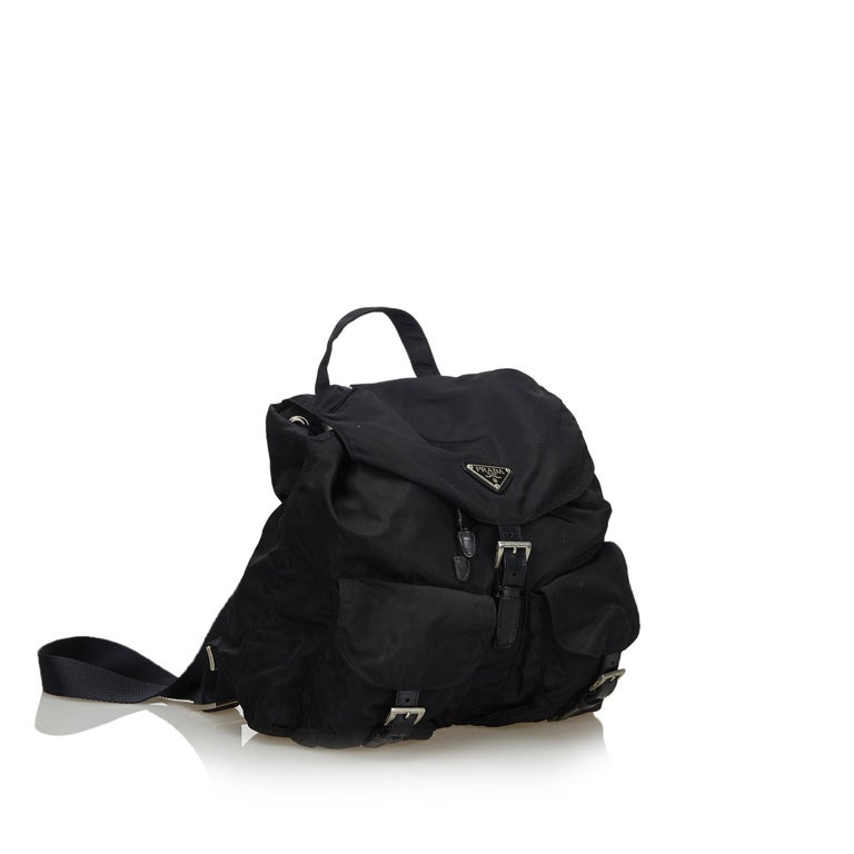 This backpack features a nylon body with leather trim, front exterior flap pockets with leather buckle closure, flat back straps, a flat top handle, a top flap with a drawstring closure, and an interior zip pocket. It carries as B+ condition