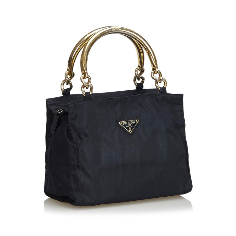 This handbag features a nylon body, gold-tone metal handles, a top zip closure, and interior zip pockets. It carries as B+ condition rating.  Inclusions:  Authenticity Card Dimensions: Length: 20.00 cm Width: 25.00 cm Depth: 14.50 cm Hand Drop: