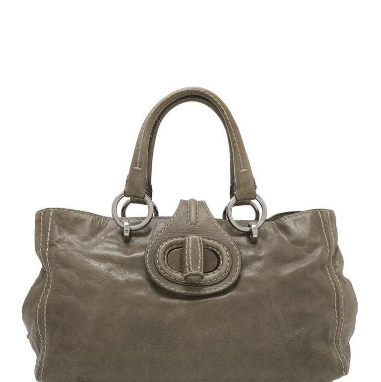This handbag features an aged calfskin body, silver-tone hardware, slot through snap closure, double top handles, a side snap tabs for expandability, fabric lining, and interior zip and slip pockets. It carries as B condition rating.  Inclusions: