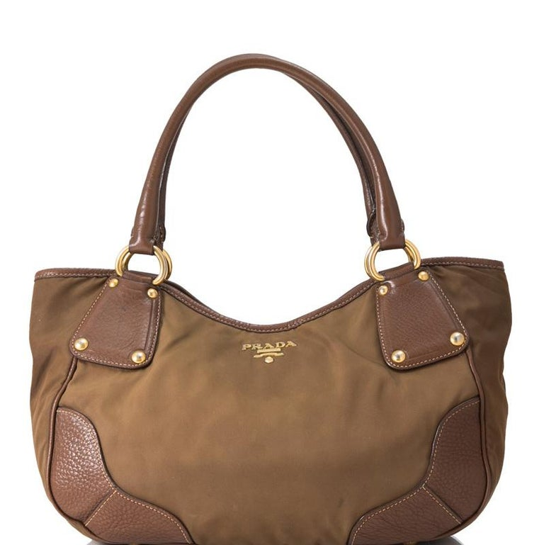 This shoulder bag features a nylon body, gold-tone hardware, double top handles, a snap tab closure, protective metal feet, leather and fabric lining, and interior zip and slip pockets. It carries as B condition rating.  Inclusions:  This item does
