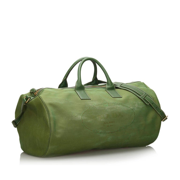 This duffle bag features a canvas body with leather trim, rolled leather handles, a detachable flat leather strap, a top zip closure, and an interior zip pocket. It carries as B condition rating.  Inclusions:  This item does not come with