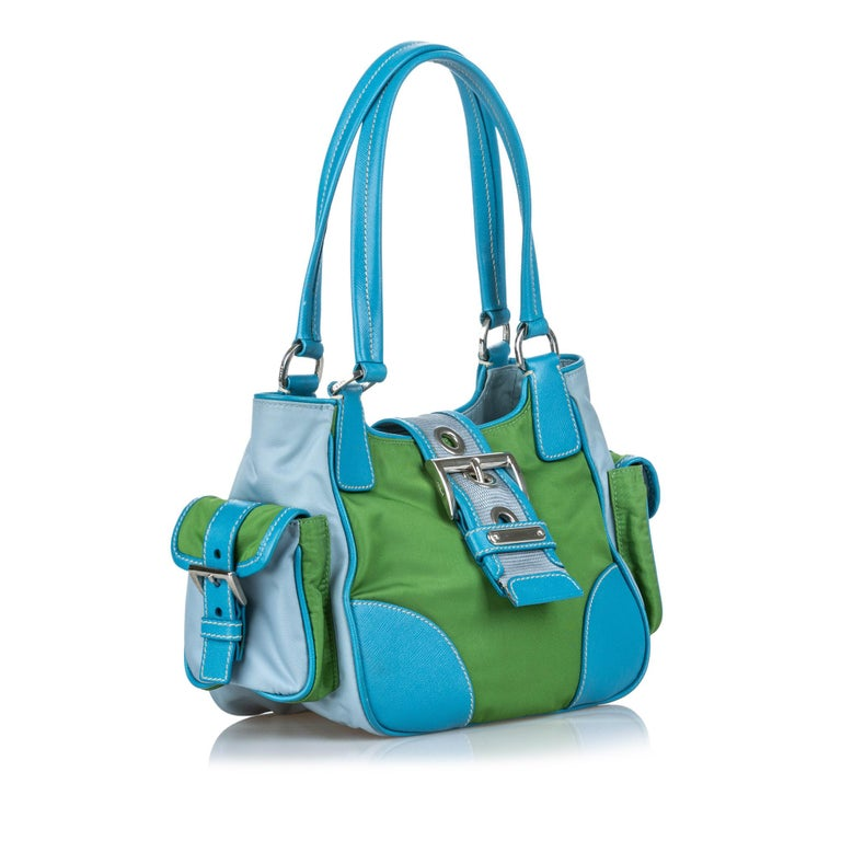 This shoulder bag features a nylon body with leather trim, side exterior flap pockets, flat leather handles, a top strap with a buckle closure, and an interior zip pocket. It carries as B+ condition rating.  Inclusions:  This item does not come with