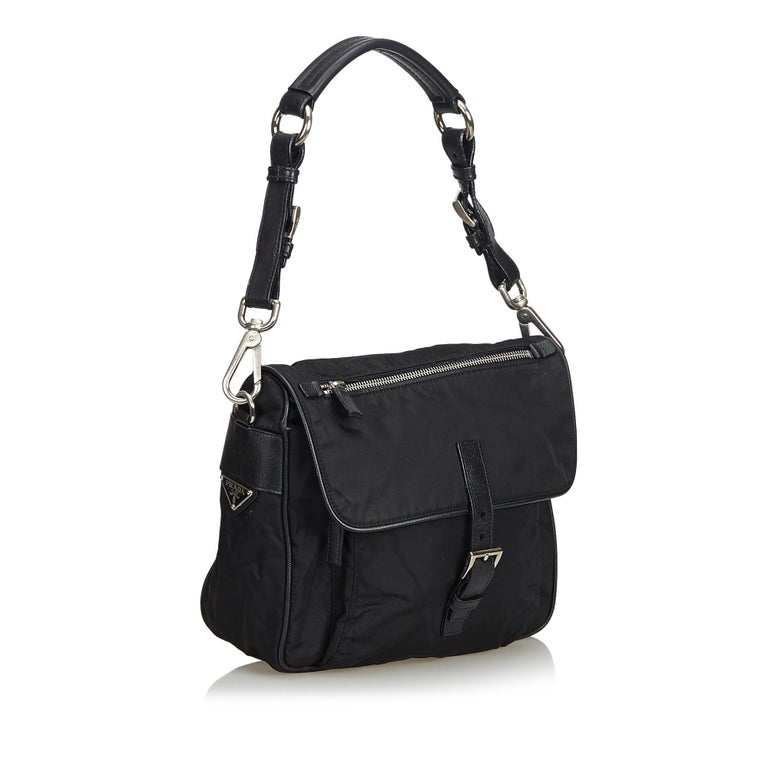 This shoulder bag features a nylon body, front exterior zip pocket, a flat leather strap, and an interior zip pocket. It carries as B+ condition rating.  Inclusions:  Dust Bag Authenticity Card  Dimensions: Length: 20.00 cm Width: 23.00 cm Depth:
