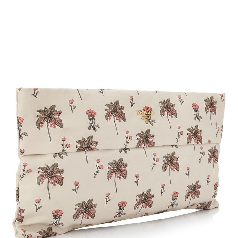 This clutch bag features a printed fabric body, gold-tone hardware, a hand slot, a top zip closure, fabric lining, and interior zip and slip pockets. It carries as AB condition rating.  Inclusions:  This item does not come with