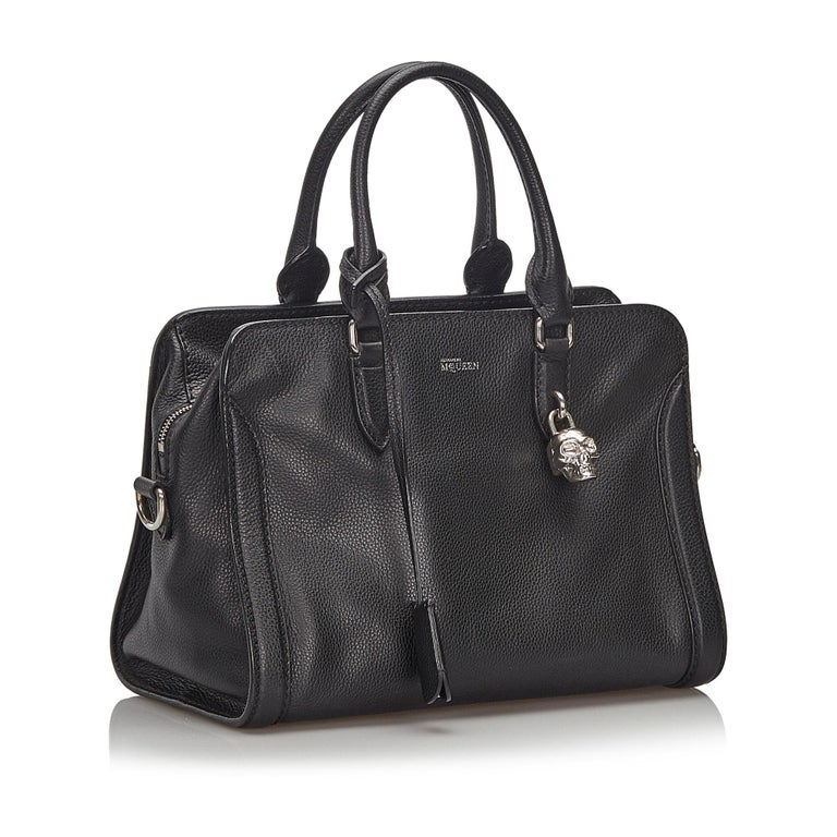 This Skull Padlock satchel features a calfskin leather body, rolled leather handles, a flat leather strap, a top zip closure, and interior zip and slip pockets. It carries as AB condition rating.  Inclusions:  Dust