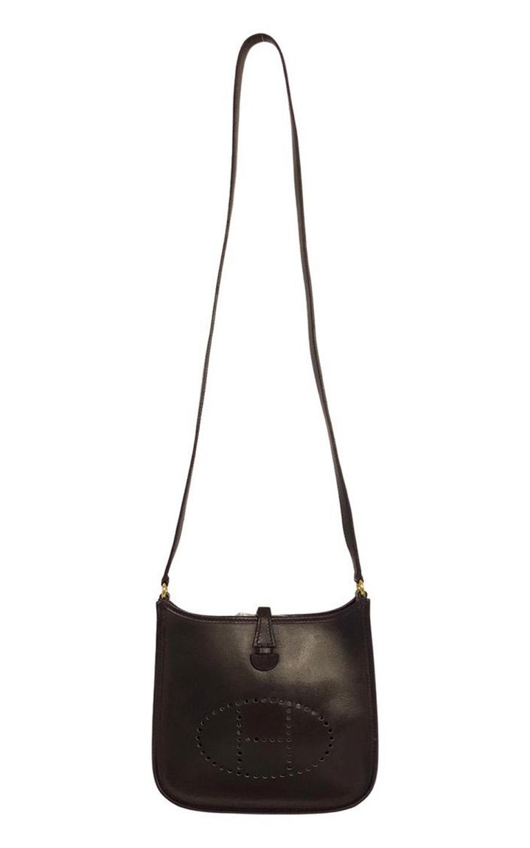 Hermès Evelyne TPM in Amarante colored leather. The hardware is gold-colored. The bag closes with a push-button and has no pockets on the inside. It can be worn on the shoulder or as a crossbody bag. The shoulder strap is made of leather and is not