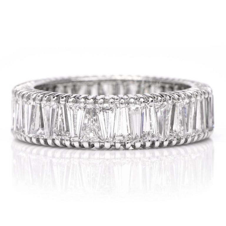 This vintage diamond eternity band ring is crafted in solid platinum. This shimmering ring features approx. 41 genuine tapered baguette shaped diamonds approx. 5.50 carats, H-I color, VS clarity. Measures 2mm height x 5.50 mm wide and weighs 5.5
