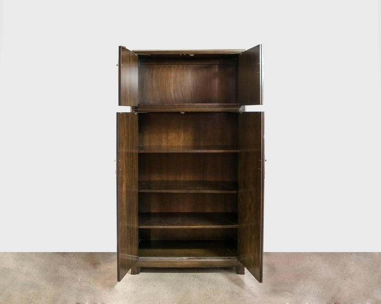 Baker Armoire, circa 1980, from their Far East collection. Made of mahogany with solid brass trim and hardware, in excellent vintage condition.