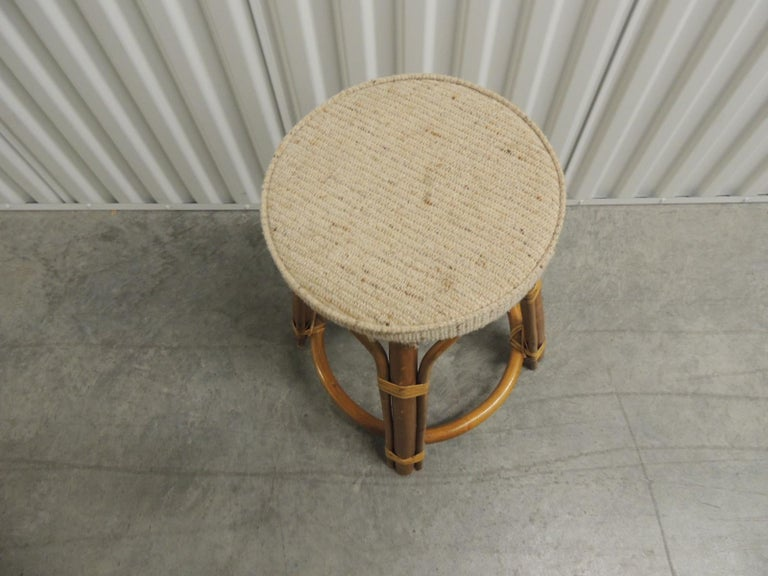Vintage bamboo and rattan tall stool with upholstered round seat. Bent bamboo tall stool with vintage beige grain sack fabric round seat. Rattan details. Size: 19.5 H x 12 D (base 18