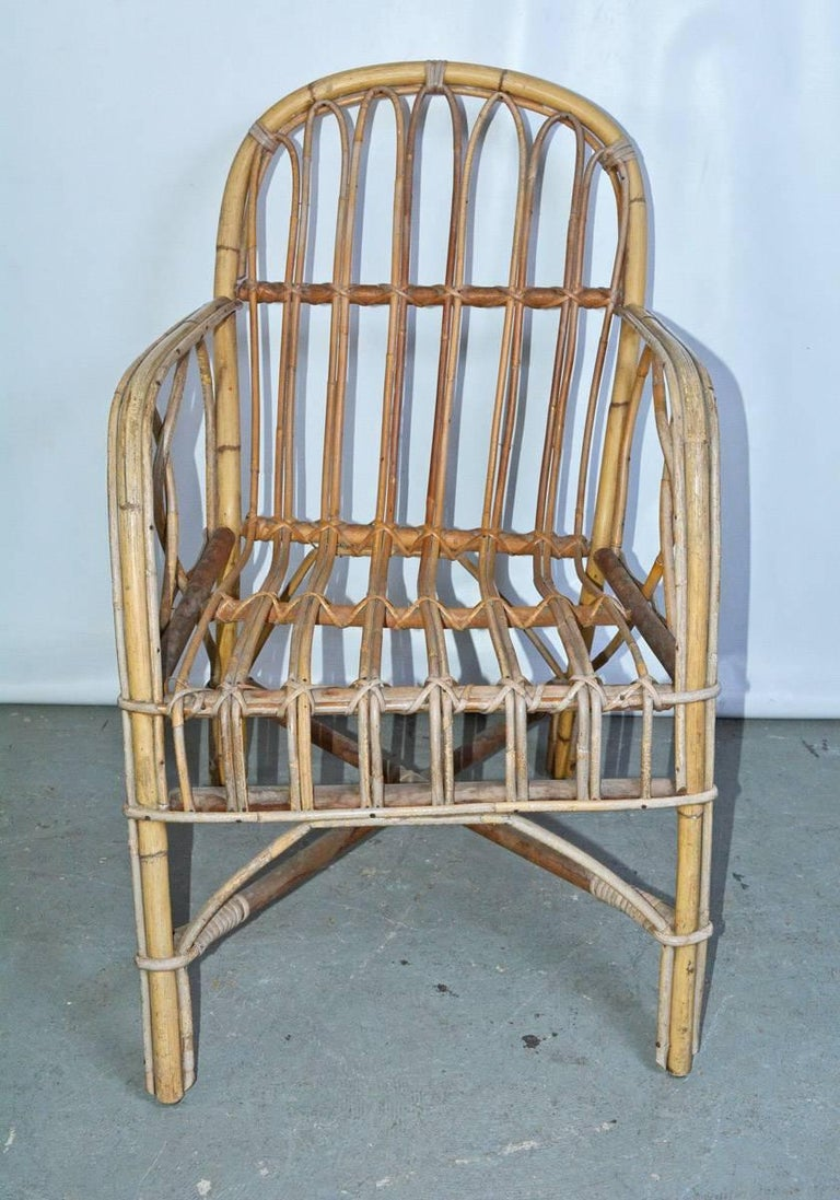 Bamboo rattan armchair with rounded back and arm.