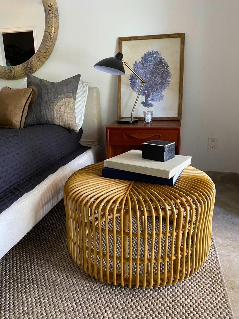 Vintage hand-crafted round bamboo coffee table or ottoman with rattan accents and contemporary Organic Modern design. Rounded form with flat sides features bent bamboo with open slats running in opposite directions, creating a geometric pattern.