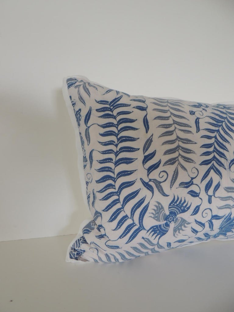 Bolster floral blue and white throw pillow depicting birds and fern in the front textile. Throw pillow in light and dark shades of blue. Pillow embellished with ATG custom white cotton flat trim all around. Decorative bolster pillow finished with